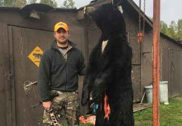 Man With Crossbow And Black Bear